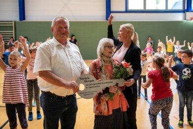 Bürgermeister Thomas Arnold (vorn v. l.), die Namensgeberin Roselore Sonntag und Schulleiterin Silke Simon nehmen mit den Grundschülern aus Geringswalde die neue Turnhalle in Besitz.