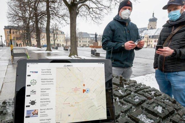 """Enrico Haustein (rechts) und Christian Gerlach testen auf dem Marienberger Markt die App """"MeinERZ""""."""