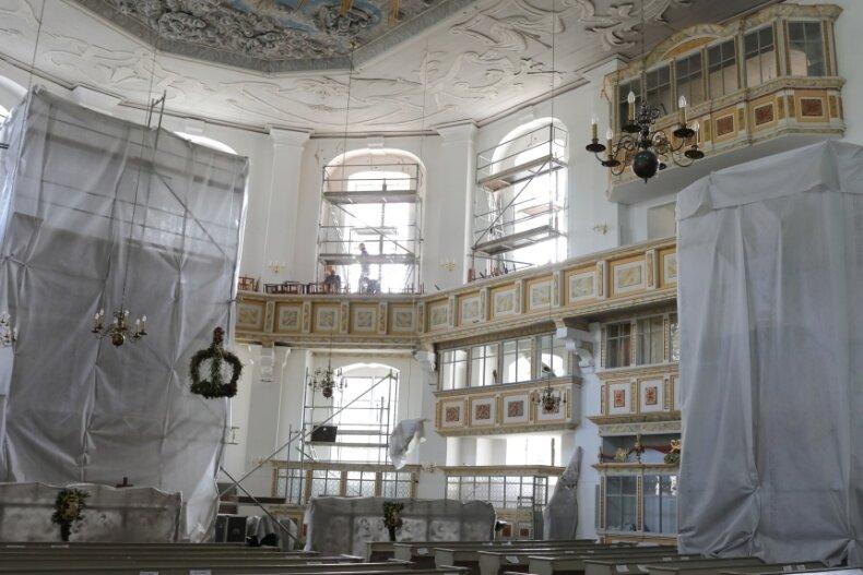 Weil das Bohren für die neuen Anker im Mauerwerk nur trocken erfolgen kann, wurden Altar, Kanzel und die Orgel mit einem atmungsaktiven Vlies verhüllt, um den Staub abzuhalten.