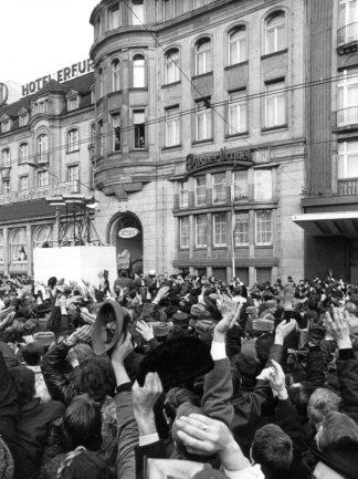 """Eine Menschenmenge hat sich am 19. März 1970 vor dem Hotel """"Erfurter Hof"""" versammelt, um dem damaligen deutschen Bundeskanzler Willy Brandt, der sich nach minutenlangen Ovationen am Fenster zeigte, (M) zuzujubeln. Vor 50 Jahren, am 19. März 1970, kam mit Willy Brandt erstmals ein Bundeskanzler zu einem Staatsbesuch in die DDR. Mit der Visite verbanden viele Menschen Hoffnungen und zeigten dies bei dem historischen Ereignis in Erfurt."""