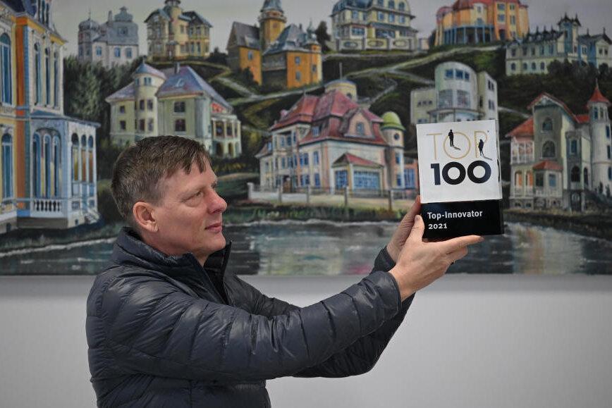 Symbiose zwischen Vergangenheit und Zukunft: Vorstandschef Uwe Bauch hält den Top-100-Award vor einem Bild des Chemnitzer Künstlers Wieland Weberin den Händen. Es zeigt die bekanntesten Villen der Stadt.