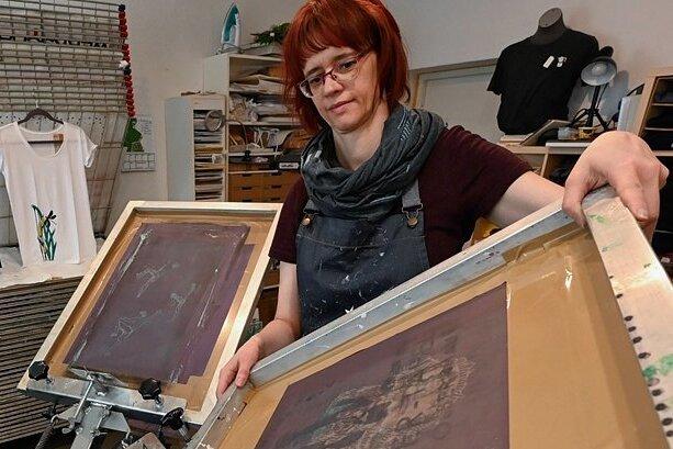 Grafikerin Peggy Albrecht bei der Einrichtung des Siebdruck-Karussells für das Bedrucken von Textilien.