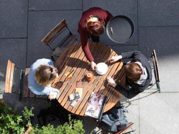Eine Kellnerin bedient in einem Cafe zwei Frauen.