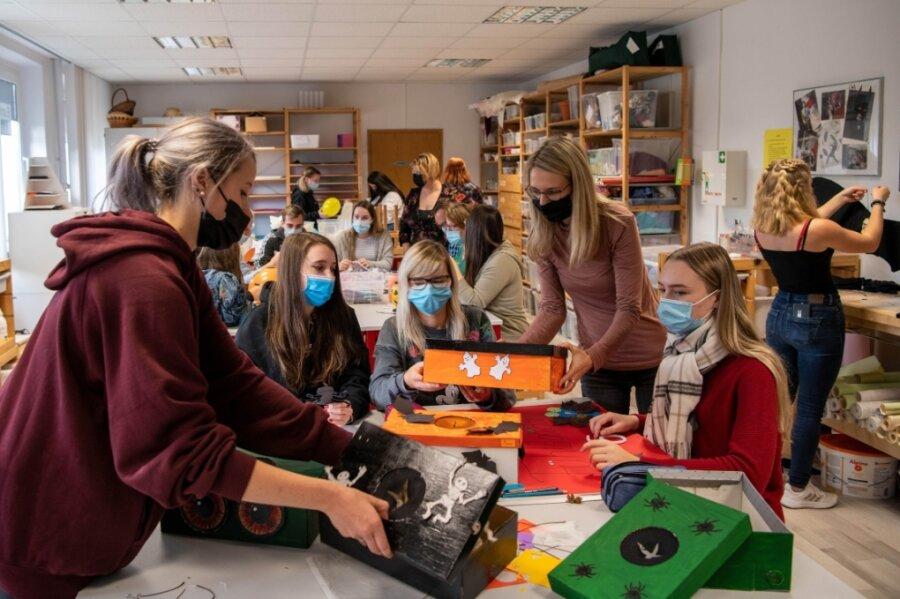 Schüler und Lehrkräfte arbeiten im Kreativraum der Euro-Akademie an Dekorationen und Spielen.