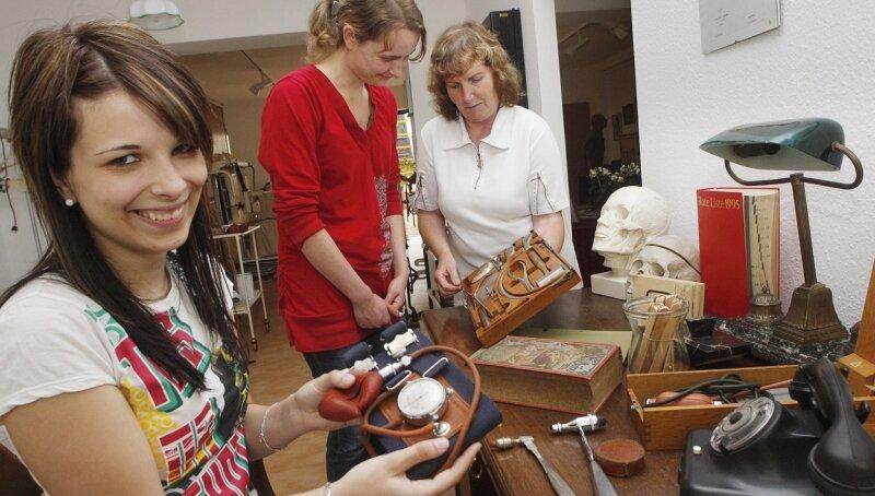 """<p class=""""artikelinhalt"""">Ursula Friedemann (rechts) vom Museumsverein zeigt den Besucherinnen Antje Freitag (links) und Nancy Tischendorf ein Blutdruckmesser und chirurgisches Besteck. Die medizinischen Gerätschaften wurden in den 1940er-Jahren eingesetzt und sind am Dienstag im Museum Arztpraxis zu sehen.</p>"""