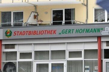 Handwerker haben ein Schild mit dem neuen Namen über der Tür der Bücherei in Limbach-Oberfrohna angebracht.