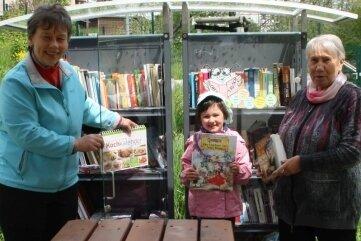 """Kerstin Franke (l.) und Tamara Eidenschink gehören zu den Initiatoren der """"Schmökerbox"""" an der Wanderhütte in Dänkritz. Die fünfjährige Lena hält in der ausgedienten Kühlzelle Ausschau nach Kinderbüchern."""