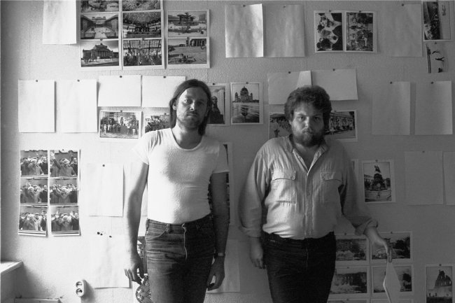 Der in Jena geborene Schriftsteller Lutz Rathenow (rechts) und der aus Sachsen stammende Fotograf Harald Hauswald 1986 vor einer Wand, an der Fotos aus ihrem Ostberlinbuch hängen. Die beiden verstanden den Text-Bild-Band als ein Buch gegen die Mauer. 1987 ist es herausgekommen - und zwar ausschließlich im Westen.