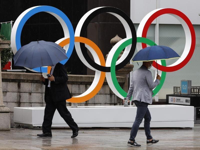 Passanten gehen an Olympischen Ringen in Tokio vorbei. Während der Spiele wird es keine Fans in den Stadien geben.