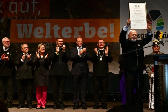 Alt-Landrat Volker Uhlig hält stolz die Welterbe-Urkunde in die Höhe.