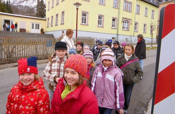 Hortkinder und Schüler der Dittersdorfer Grundschule - begleitet von Margit Bauer und Uta Drechsel - überqueren die Straße. An dieser Stelle wurde sogar die Fahrbahn eingeengt, um Kraftfahrer dazu zu bewegen, auf die Bremse zu drücken.