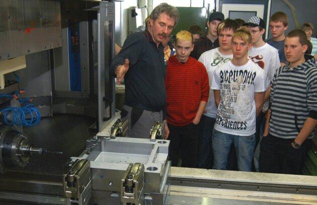 Frank Lindner (links) erklärte Mittelschülern aus Jöhstadt am Montag die Abläufe in der A-Form AG in Mildenau. Die Form- und Werkzeugbaufirma beteiligt sich seit Jahren an der Woche der offenen Unternehmen.