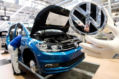 Ein Mitarbeiter zeigt ein VW Logo kurz vor Einbau in einen Volkswagen Touran.