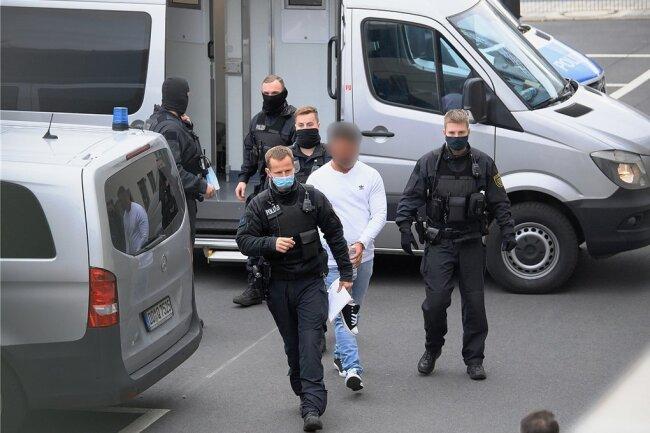 Ein Verdächtiger wird nach seiner Festnahme von Polizisten in das Gebäude des Oberlandesgerichts Dresden geführt.