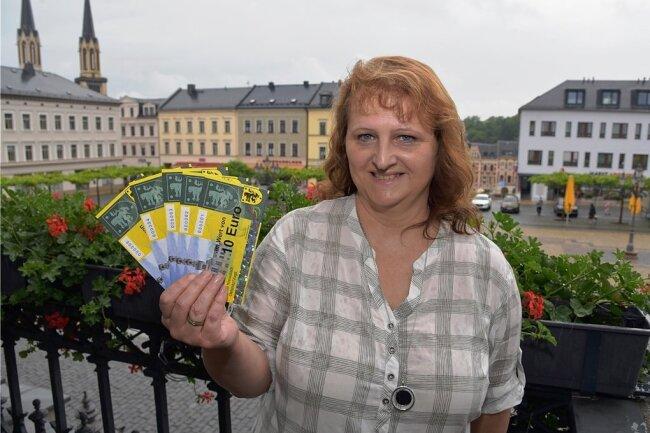 Anett Neudel, Marktmeisterin der Stadt Oelsnitz, zeigt die neuen Oelsnitz-Gutscheine.