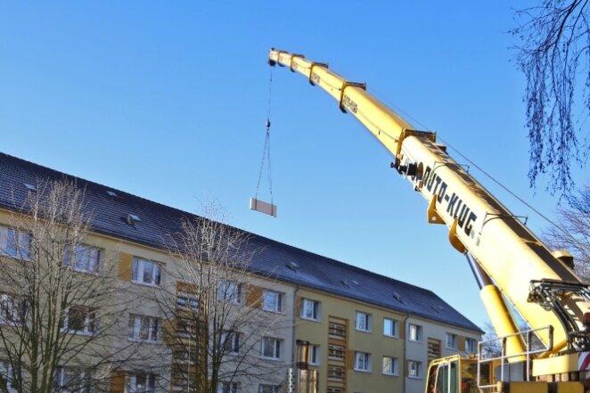 Riesenkran hebt Balkonbrüstungen über Dächer