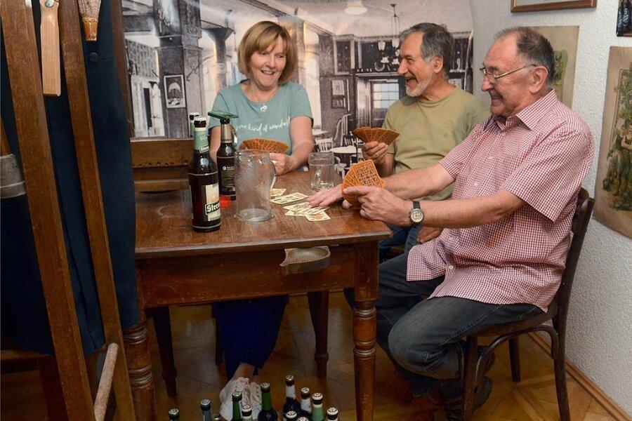 """Eine Museumskneipe gehört zur neuen Ausstellung """"Sammelsurium"""", die ab Samstag im Falkensteiner Museum zu sehen ist. Am Tisch haben Ursula Fuchs, Hans Beyer und Ulrich Wolf (rechts) Platz genommen."""