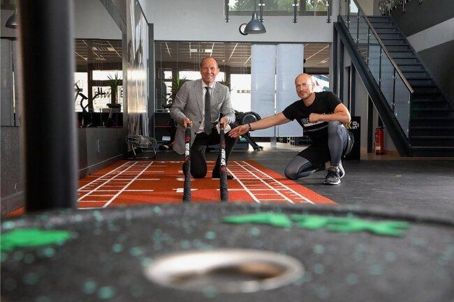 Inhaber Heiko Junghans erläutert Bürgermeister Lothar Ungerer am Donnerstagvormittag die Möglichkeiten beim Rope-Training, wo sämtliche Muskelgruppen des Oberkörpers belastet werden.