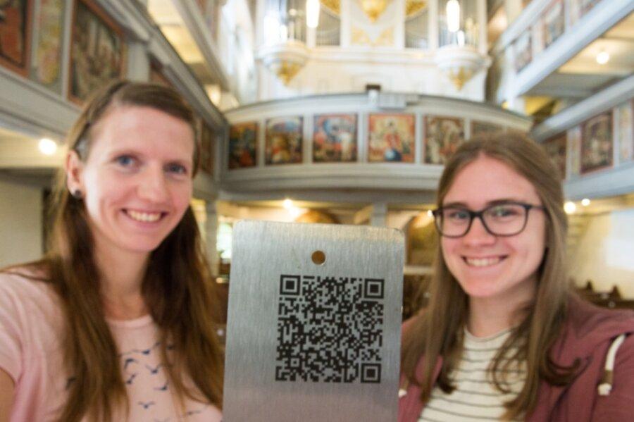 Tabea Schönfelder (l.) und Esther Schreiter mit einem der QR-Codes, der Besucher der Wehrkirche auf eine Entdeckungsreise mitnimmt. Er begrüßt die Gäste an der Pforte der Kirche.