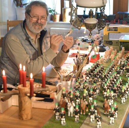 Bernd Kötter aus Freiberg schnitzt und drechselt an der Freiberger Bergparade: In seinen Händen nimmt ein Beamter mit einer Fahne farblich Gestalt an.