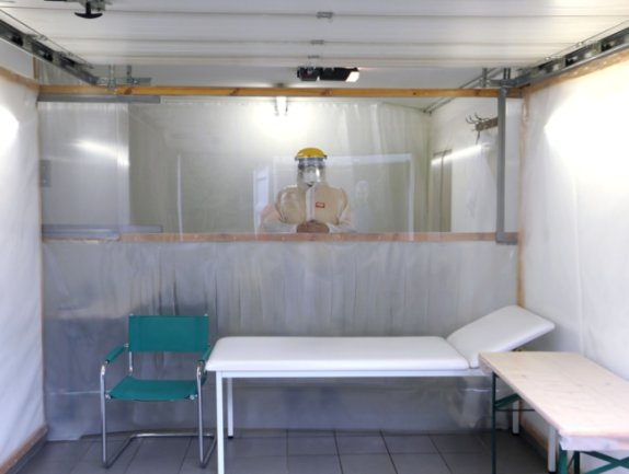 In einer Callenberger Garage behandelt Arzt Christoph Lohmann Patienten mit Covid-Symptomen. Zwischen ihnen befindet sich eine Trennwand mit Plexiglas im oberen Bereich und einem PVC-Lamellenvorhang.