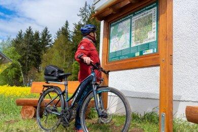 Karl Schneider aus Rebesgrün studiert die Infotafel am neuen Abschnitt des Göltzschtal-Höhenradweges, auf der über den Streckenverlauf und die Alte Königstraße informiert wird. Die Tafel samt Sitzgruppe und Panoramabild befindet sich in Höhe des Trinkwasser-Hochbehälters am Waldrand.