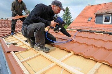 Mitarbeiter Ingo Zehmisch und Matthias Kunze (v. l.) vom Dachdeckerbetrieb Mirko Heine aus Wernsdorf decken zurzeit das Dach auf dem Anbau der Kita Langenleuba-Oberhain.