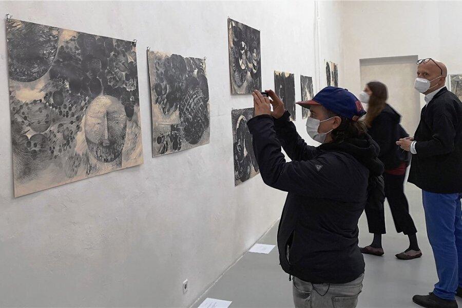 """Endlich wieder Kunst """"live"""" - die Eröffnung der Ausstellung im Weltecho mit Arbeiten von Gertrude Köhler war gut besucht. Im Vordergrund einige ihrer """"Weltraumzeichnungen""""."""