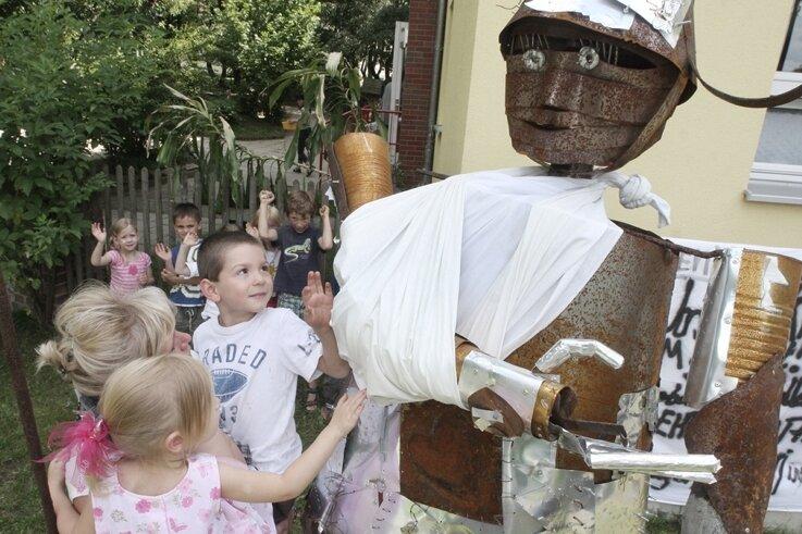"""<p class=""""artikelinhalt"""">Erzieherin Ina Schmidt mit den Kindern Norea (links) und Luka vor der Ritterfigur, die seit Dienstagmorgen wieder vollständig ist. </p>"""