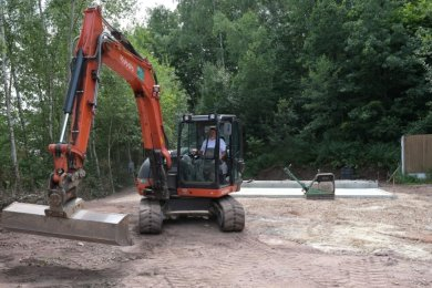 Derzeit wird das Umfeld des Blockhauses, das Ende August geliefert werden soll, gestaltet. Im Hintergrund ist die Grundplatte zu sehen.