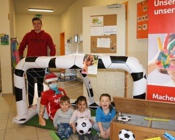 """Torhüter Leon Seefeld mit Kindern aus dem """"Haus der kleinen Füße""""."""