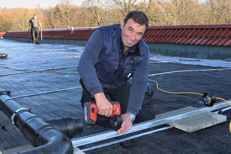 Klaus Wolf gehört zum Mitarbeiterteam der AST GmbH aus Österreich, die derzeit die neue Solaranlage auf dem Dach des Sozialgebäudes im Oederaner Freibad montieren.