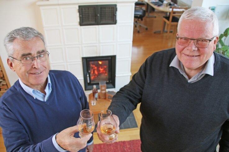 Franz-Peter Kolmschlag (l.) und Professor Michael Eßlinger stoßen mit edlem Whisky aus Freibergs Tiefen in passenden Gläsern an. In der Rathausbaude sind diese ab sofort zu erwerben.