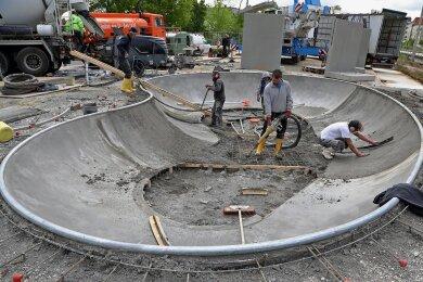 Mitarbeiter einer Firma aus Oranienbaum verteilen den Ortbeton im Skate-Bowl.