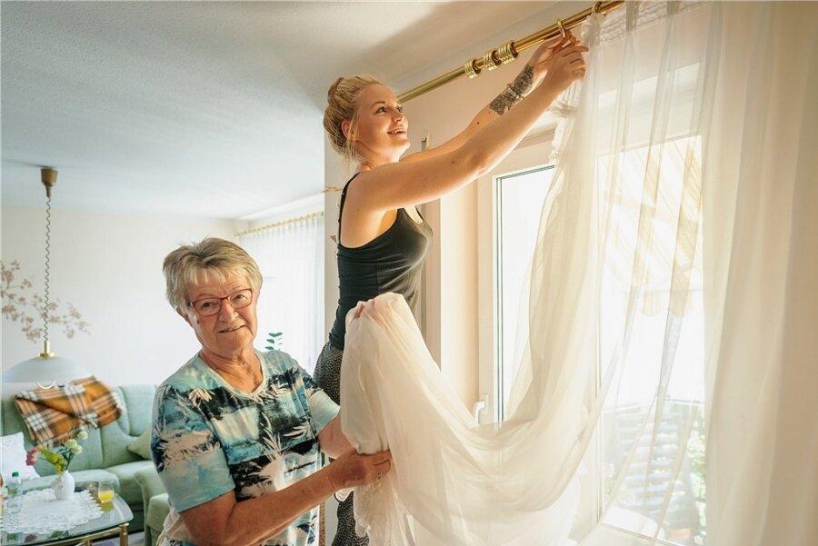 Weil es allein nicht mehr klappt: Nora Hübner hilft der Dresdner Seniorin Renate Peter beim Aufhängen der Gardinen.