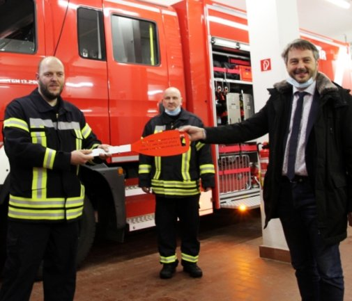 Ortswehrleiter André Weiß (l.) und Stadtwehrleiter Wolfgang Stephan (M.) erhalten von Bürgermeister Thomas Kunzmann symbolisch den Schlüssel.