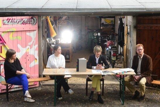 In einem Garagenhof in Bernsdorf präsentierten Buchbinderin Cornelia Ahnert (von links), Illustratorin Ulrike Schell, OB Barbara Ludwig und Bewerbungschef Ferenc Csak das Bewerbungsbuch. Die Garage dient als Symbol für die Vergangenheit, aber auch als Treffpunkt zum Reden und Tüfteln.