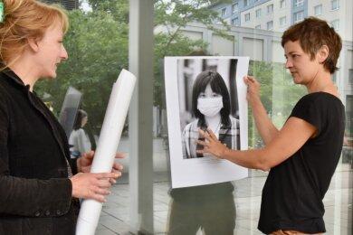 Susanne Schneider (links) und Franziska Kurz beim Anbringen der Plakate an Schaufenstern im Rosenhof.