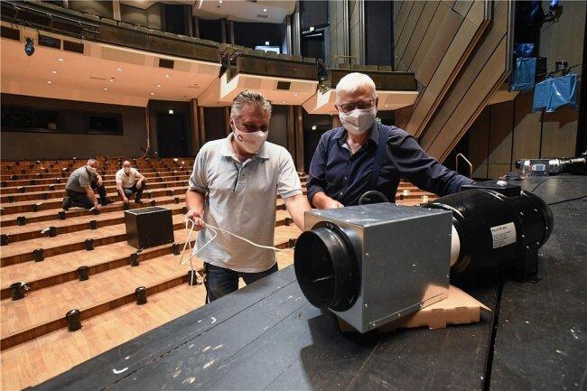 Firmeninhaber Roland Krüger und Gunther Heinrich, der an dem Projekt mitarbeitet, mit einem der Ionen-Generatoren, die nun im Opernhaus zum Einsatz kommen. Jeder Sitz im Raum (sie sind derzeit abgebaut) hat eigene Belüftungsschlitze - ein Vorteil für die neue Technik.