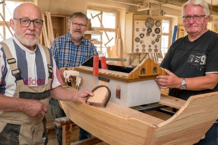 Stefan Feist, Hans-Georg Heidinger und Tischlermeister Frank Loos (v. r.) in dessen Hallbacher Werkstatt mit der im Bau befindlichen Arche, über der abschließend ein hölzerner Regenbogen angebracht wird.