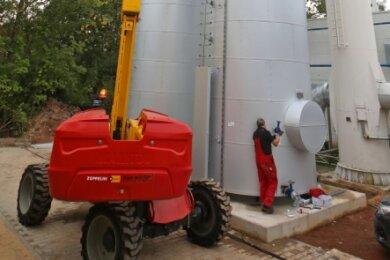 Während der 18 Meter hohe Pufferspeicher am Kran hängt, gibt der Projektleiter von der Hebebühne aus Anweisungen per Funk.