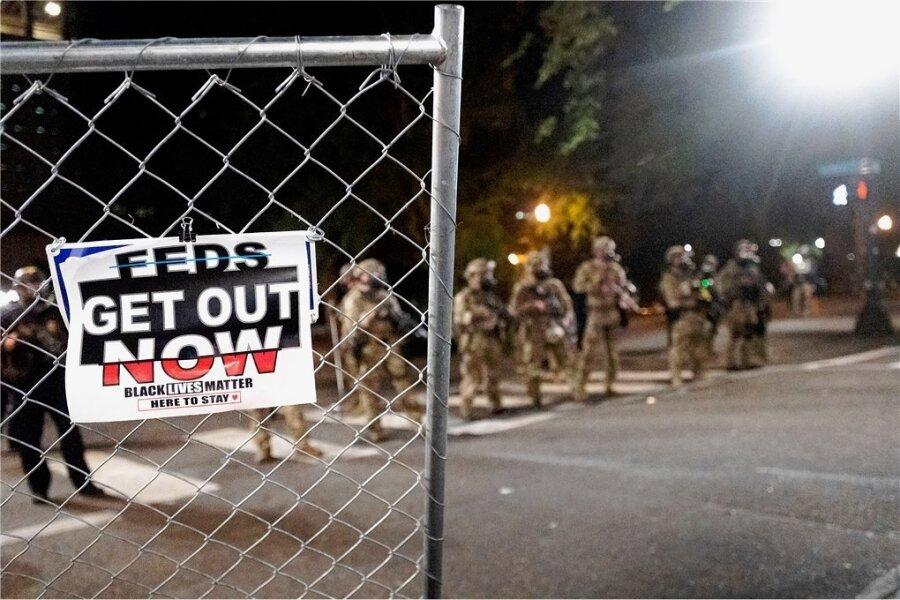 """Portland: Sicherheitskräfte treiben Demonstranten auseinander, am Zaun ist zu lesen """"Feds get out now"""" (Bundesbeamte jetzt raus)."""