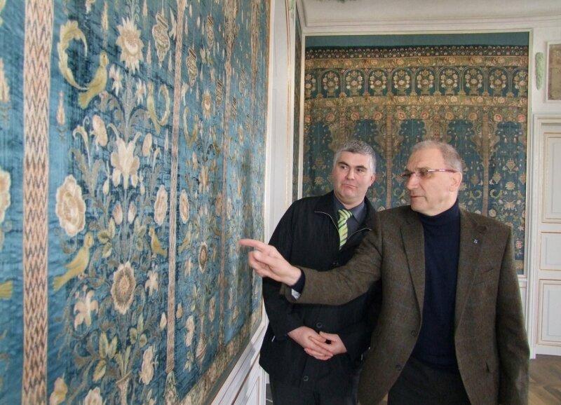 """<p class=""""artikelinhalt"""">Bürgermeister Tino Kögler (links) und Freundeskreisvorsitzender Karl Weiß sind vom Aussehen der einzigartigen blauen Seidentapete beeindruckt. Darauf finden sich üppige Blumenbouquets, exotische Vögel und schwingende Öllampen. </p>"""