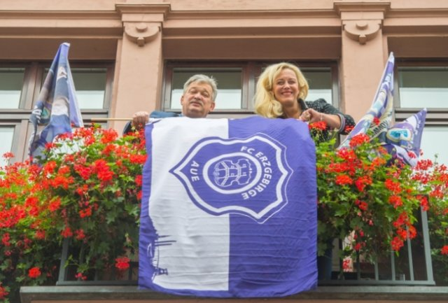 Aus dem Rathaus in Aue wird die Aktion der Fans zum 75. Gründungstag unterstützt. Oberbürgermeister Heinrich Kohl und Pressesprecherin Jana Hecker haben auch bereits Erfahrung im Schmücken des Rathausbalkons, wie dieses Foto von 2019 zeigt. Damals hüllte sich das Erzgebirge vor dem Derby gegen Dynamo Dresden in Lila-Weiß.