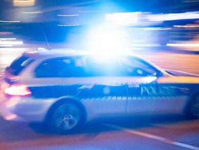 Ein Polizeiauto fährt unter Einsatz von Blaulicht und Sirene eine Straße entlang.