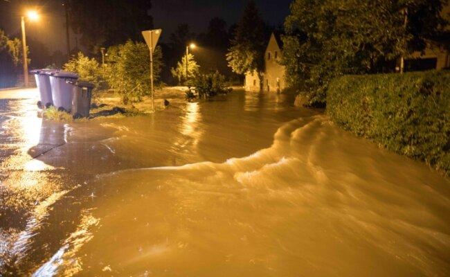Der Münzbach trat über die Ufer und verwandelte die Straße in einen Fluss. Das schlammige Wasser überspülte Grundstücke und drang in Gebäude ein.