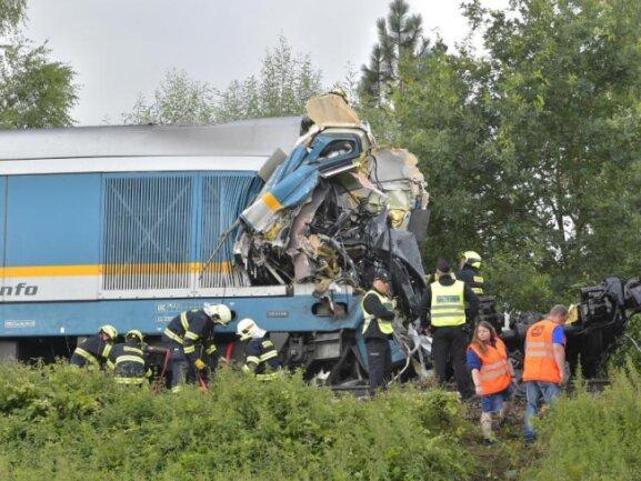 Einsatzkräfte stehen an einem zerstörten Waggon in Tschechien.