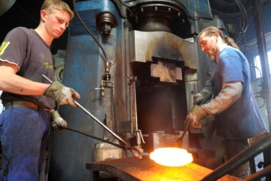 """<p class=""""artikelinhalt"""">Louis Stasche (links) und Rico Menzel holen das glühende Eisen aus dem Ofen und bearbeiten es mit einem Gesenkhammer. Daraus entstehen soll ein Außenring für ein Kugellager einer großen Maschine. Der Handwerksbetrieb beteiligt sich an der Umweltwoche in Berlin.</p>"""