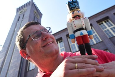Felix Prehl zeigt vor dem Uhrenturm des Wirkbau-Geländes einen besonderen Nussknacker.