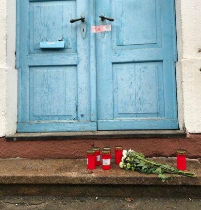 Vor der Haustür liegen Blumen.